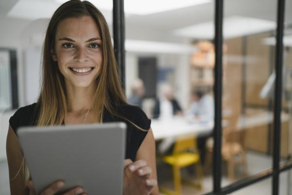 junge geschaeftsfrau im buero mit digitalem