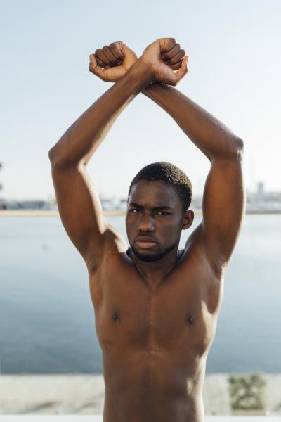 schwarzer mann hebt gekreuzte haende