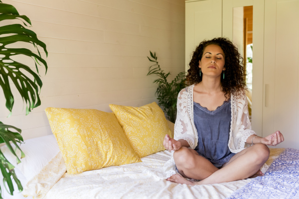 entspannte junge frau meditiert waehrend sie
