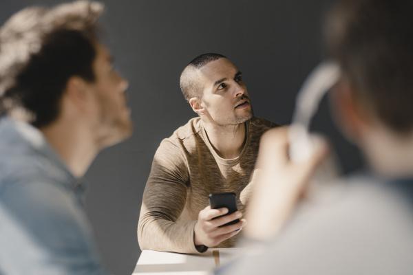 jungunternehmer in einem meeting mit smartphone