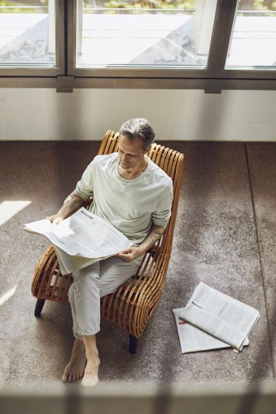 senior mann sitzt auf stuhl in