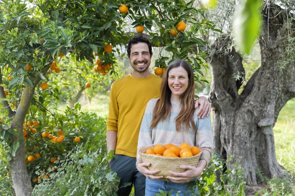 laechelndes paar mit orangen die auf