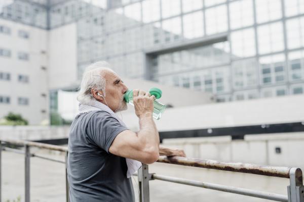 senior mann trinkwasser waehrend am gelaender