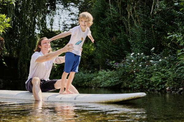 gluecklicher vater haelt jungen auf paddleboard