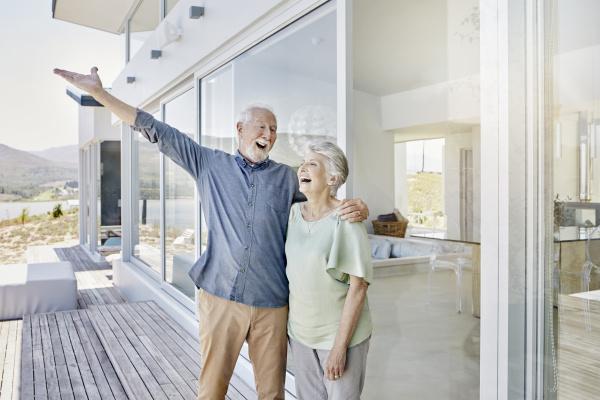 unbeschwertes seniorenpaar steht im luxurioesen strandhaus