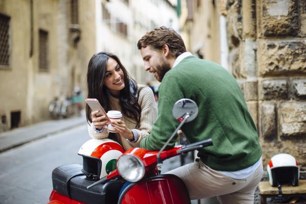 laechelnde frau zeigt smartphone zu freund