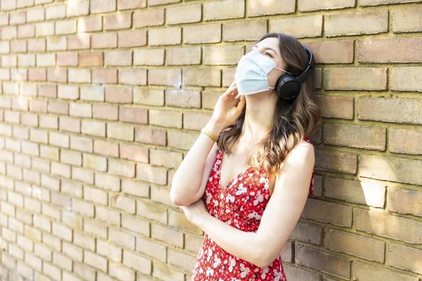 junge frau traegt schutzmaske und hoert