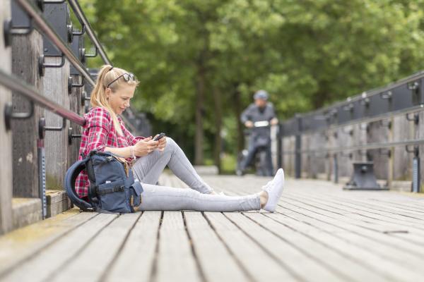 mittlere erwachsene frau mit smartphone waehrend
