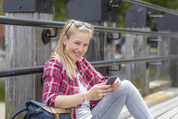 laechelnde mittlere erwachsene frau mit smartphone