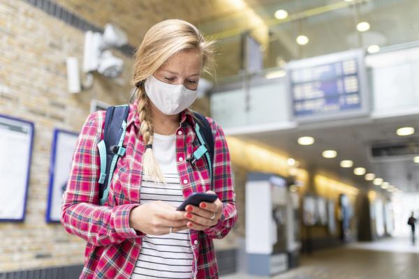 frau traegt maske mit smartphone waehrend