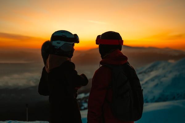 silhouette von zwei personen mit skihelmen