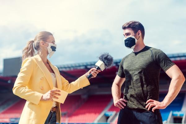 reporter interviewt fussballspieler waehrend covid 19