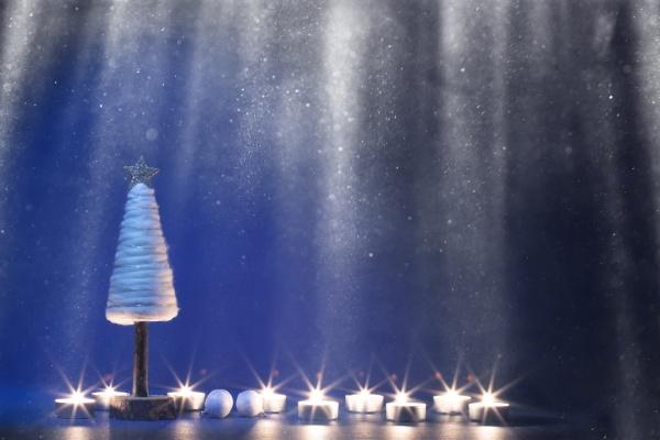 weihnachtsbaum mit kerzen bei schneefall