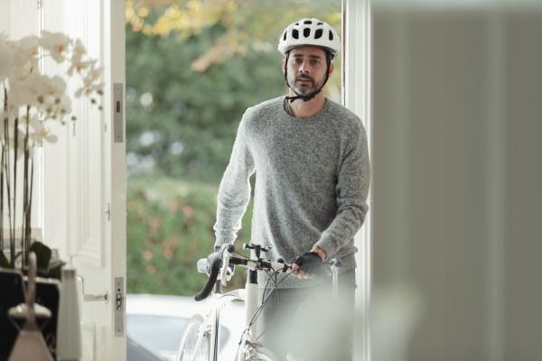 mann mit fahrrad kehrt durch haustuer