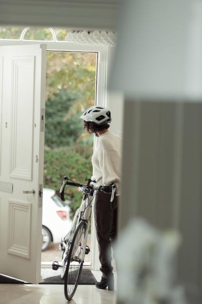 frau mit fahrrad kehrt durch haustuer
