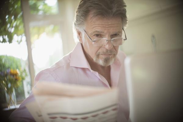 senior mann lesen zeitung am laptop