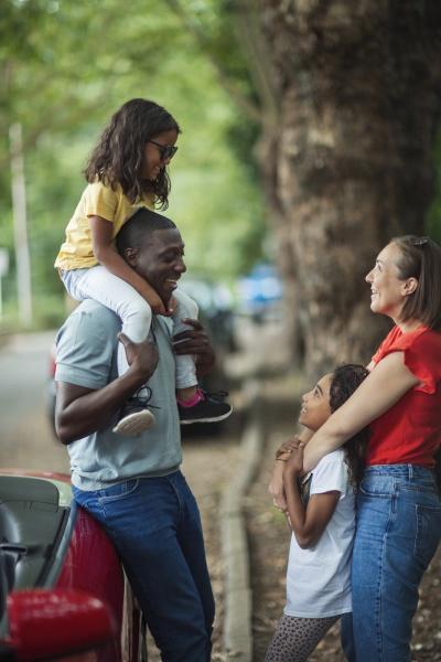 glueckliche familie ausserhalb cabrio