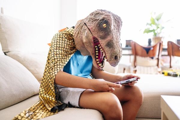 junge traegt dinosaurier maske und umhang