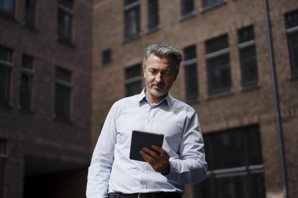 geschaeftsmann mit digitalem tablet waehrend er