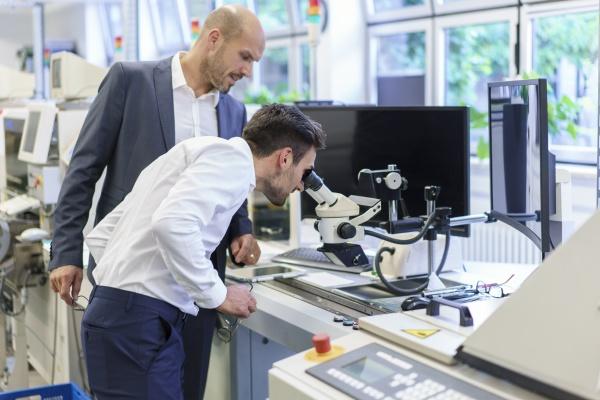 junger ingenieur der durch das mikroskop