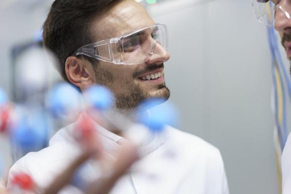 laechelnder maennlicher wissenschaftler mit molekularer struktur