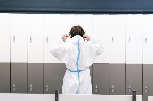 mittlerer erwachsener mann traegt schutzkleidung im