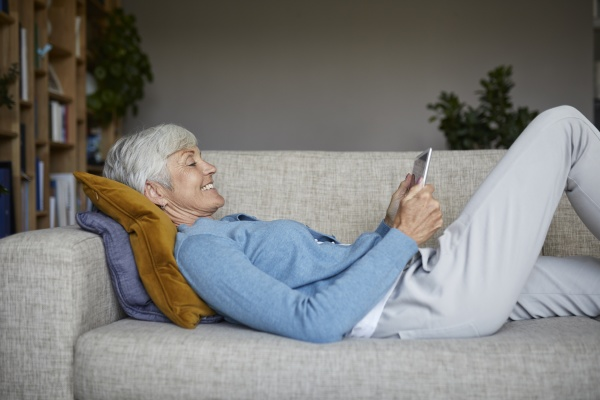 laechelnde frau mit digitalem tablet waehrend