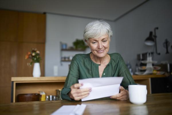 seniorin liest brief waehrend sie zu