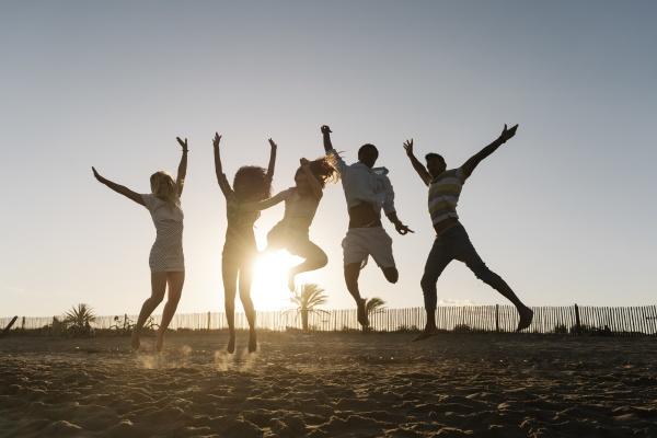 freunde springen vor freude am strand