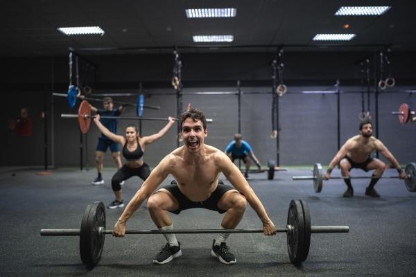athleten pfluecken langhantel beim training im