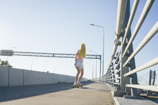 junge frau skateboarding auf bruecke gegen