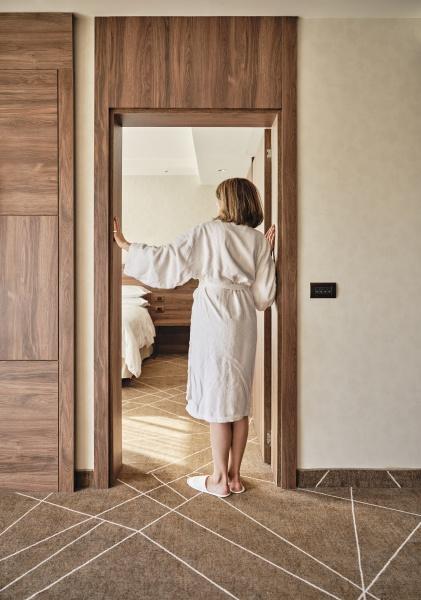 seniorin im bademantel steht vor hotelzimmertuer