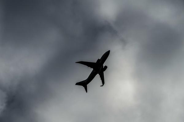 bewoelkter himmel und flugzeugsilhouette