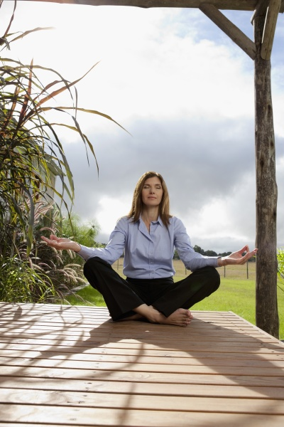 geschaeftsfrau meditiert in einem park