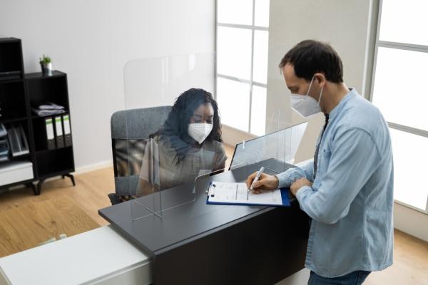 hotelrezeption durch medizinische maske geschuetzt