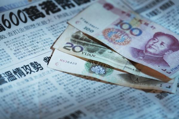 nahaufnahme chinesischer waehrung auf einer zeitung