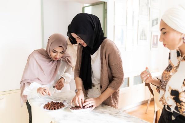 junge muslimische frauen arrangieren einen teller