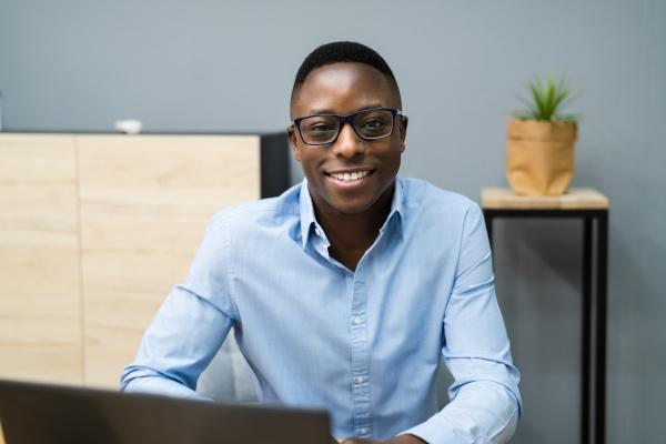 gluecklicher professioneller afrikanischer mitarbeiter mit computer