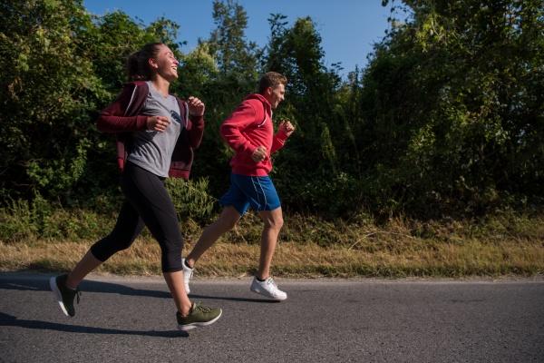 junges paar joggt auf einer landstrasse