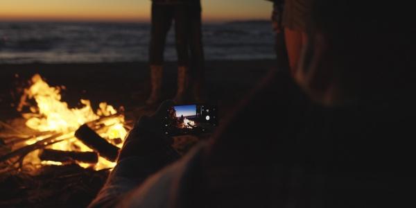 paar fotografiert am lagerfeuer am strand