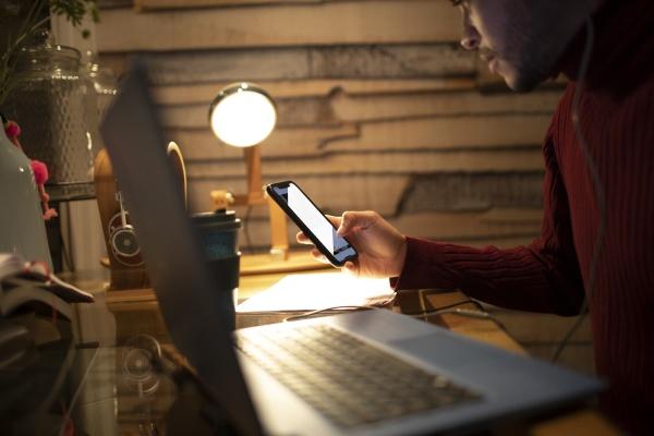 junger mann mit smartphone am laptop