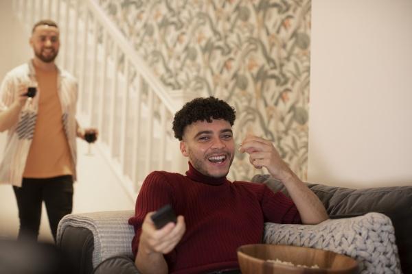 gluecklicher junger mann mit fernbedienung fernsehen