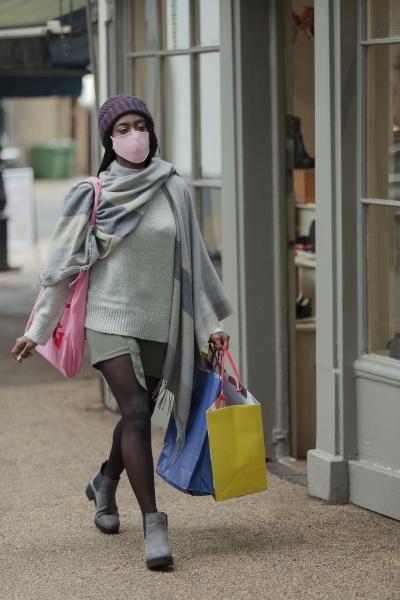 junge frau in gesichtsmaske mit einkaufstaschen
