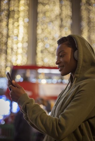 junge frau im kapuzenpullover mit smartphone