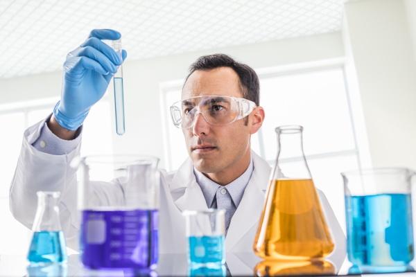 wissenschaftler betrachtet blaue fluessigkeit im labor