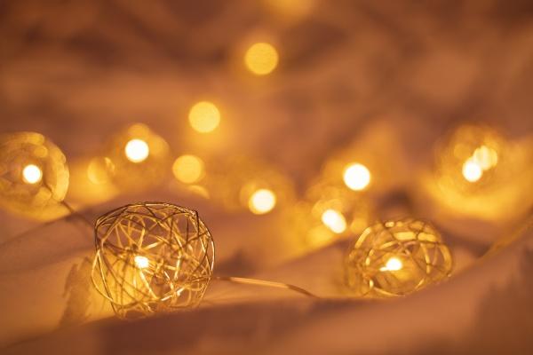 goldene verschwommene weihnachtsbeleuchtung auf zerknitterten bettlaken