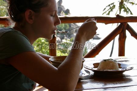 frau geniesst essen auf terrasse vor