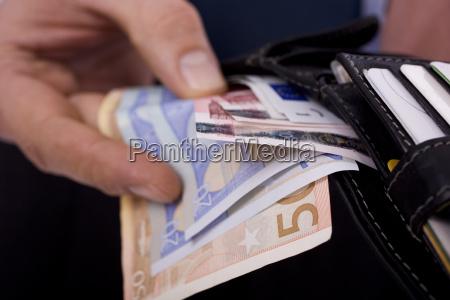 geschaeftsmann mit geldscheinen