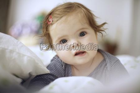 little girl between pillow