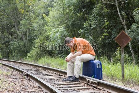 mann sitzt auf koffer auf gleisen